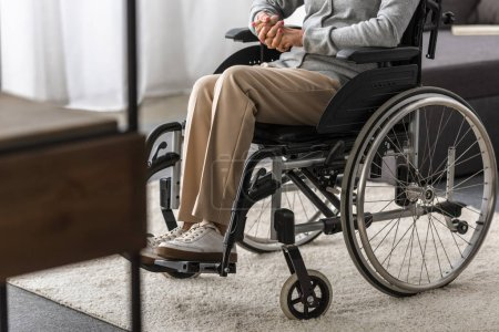 Photo for Partial view of disabled senior woman in wheelchair at home - Royalty Free Image