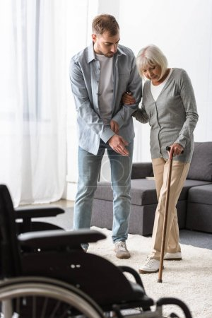 Photo pour Vue pleine longueur de l'homme aidant la mère aînée avec la canne à la maison - image libre de droit