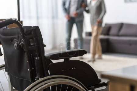 Photo for Selective focus of adult son and senior mother with wheelchair on foreground - Royalty Free Image