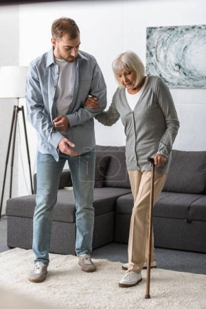 full length view of man helping senior mother with cane at home