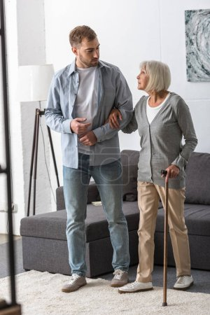Photo for Full length view of man helping senior mother with cane at home - Royalty Free Image