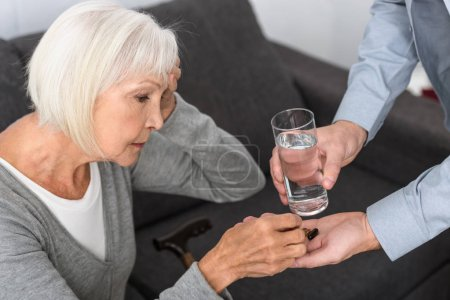 Photo for Cropped view of man giving to senior mother glass of water and medicine - Royalty Free Image