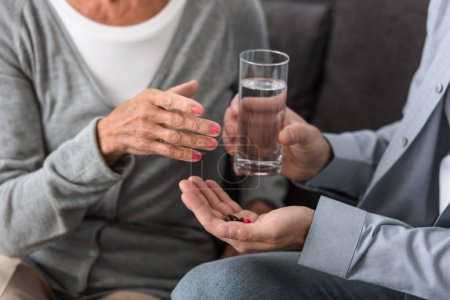 cropped view of man giving to senior mother glass of water and medicine