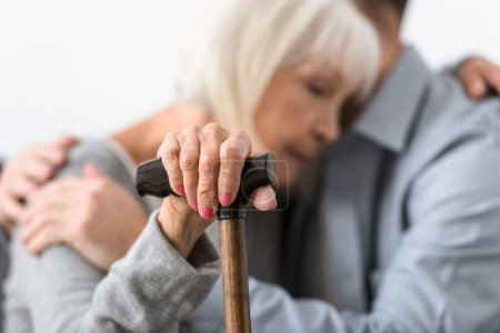 Photo for Selective focus of man embracing senior mother with cane - Royalty Free Image
