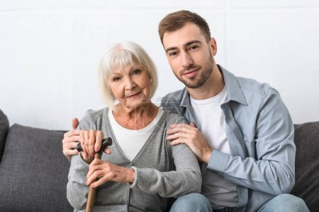 Photo pour Homme s'asseyant sur le sofa et embrassant la mère aînée dans le salon - image libre de droit