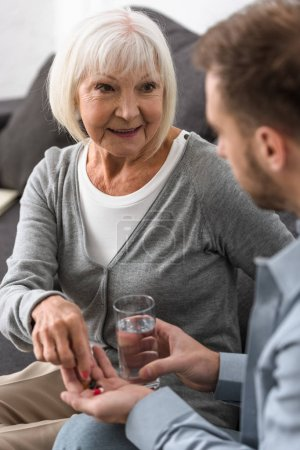 cropped view of man giving to senior mother glass of water and pills