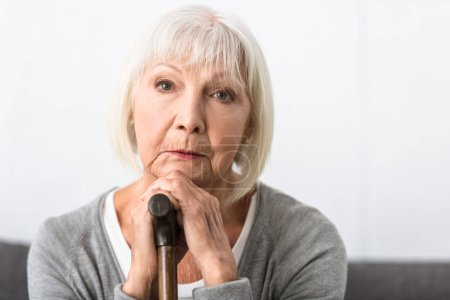 Photo for Pensive senior woman with wooden cane looking at camera - Royalty Free Image