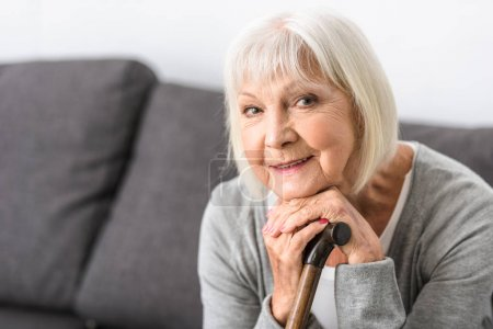 Photo for Smiling senior woman with wooden cane looking at camera - Royalty Free Image