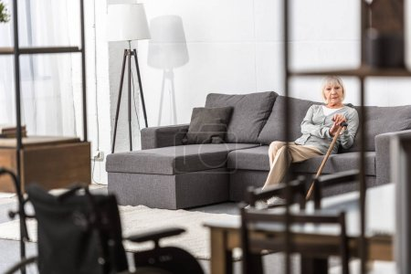 Foto de Senior woman with walking stick sitting on sofa in living room - Imagen libre de derechos