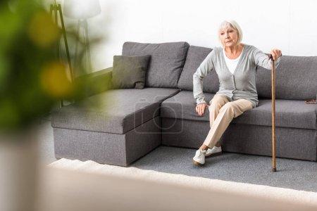 Photo pour Femme aînée avec le bâton de marche s'asseyant sur le sofa dans le salon - image libre de droit