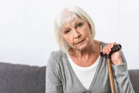 Photo pour Femme aînée pensive avec la canne en bois regardant l'appareil-photo - image libre de droit