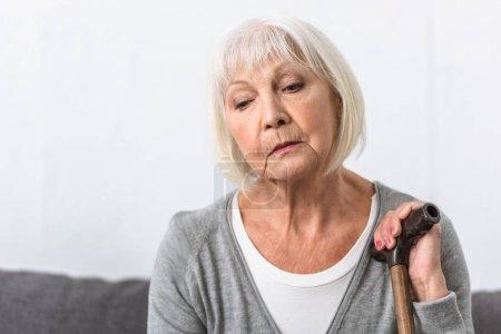 Photo pour Femme aînée pensive avec la canne en bois regardant vers le bas - image libre de droit