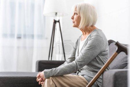 Photo pour Femme aînée pensive avec la canne en bois s'asseyant sur le sofa dans le salon - image libre de droit