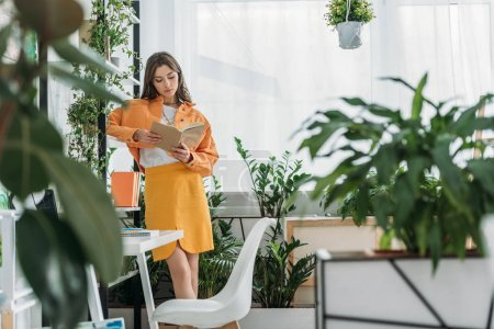 Photo for Selective focus of young fashionable woman reading book in room decorated with green potted plants - Royalty Free Image