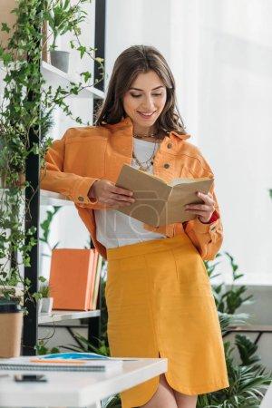 Foto de Mujer alegre leyendo libro mientras está de pie cerca de estante con plantas en maceta - Imagen libre de derechos