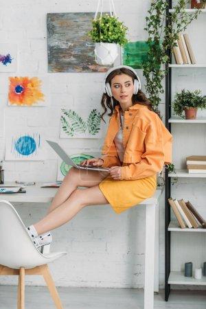 Photo pour Jeune femme branchée dans les écouteurs à l'aide d'un ordinateur portable tout en étant assis sur le bureau à la maison - image libre de droit