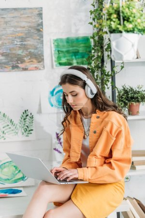 Photo for Attentive girl in headphones using laptop while sitting on desk at home - Royalty Free Image