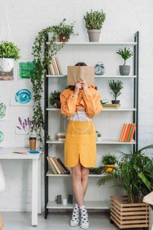 Photo pour Jeune femme à la mode debout bu rack et se cachant la face derrière le livre - image libre de droit