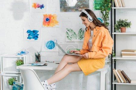 Photo pour Souriant femme à la mode dans les écouteurs à l'aide d'un ordinateur portable tout en étant assis sur le bureau - image libre de droit