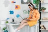 """Постер, картина, фотообои """"улыбается модная женщина в наушниках с помощью ноутбука, сидя на столе"""""""