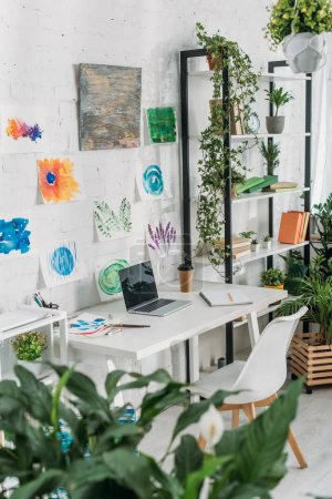 Photo for Selective focus of selective focus of spacious room with laptop on table, paintings on wall and rack with potted plants - Royalty Free Image