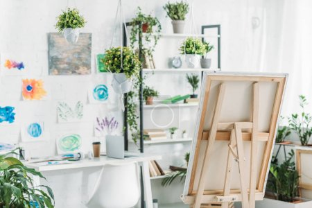 Photo for Spacious room with rack, easel, potted plants and paintings on wall - Royalty Free Image