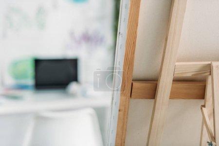 Photo pour Foyer sélectif de chevalet en bois avec toile fixe et ordinateur portable avec écran blanc - image libre de droit