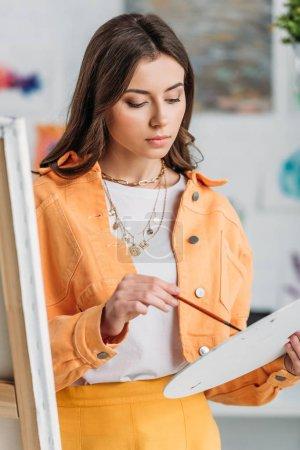Photo pour Attrayant artiste pensif tenant la palette et le pinceau tout en restant près du chevalet - image libre de droit