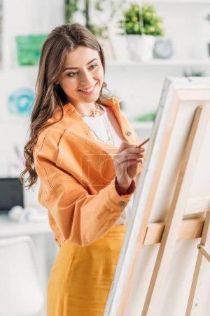 Photo pour Jeune artiste gai dans la peinture de vêtement à la mode sur le chevalet à la maison - image libre de droit