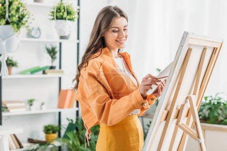 Photo pour Jeune artiste qui sourit en dessinant sur toile avec un pinceau - image libre de droit