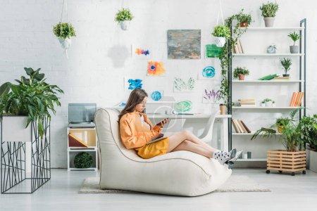 Photo pour Jeune femme utilisant un ordinateur portable et un smartphone tout en étant assis sur une chaise longue dans une chambre spacieuse - image libre de droit