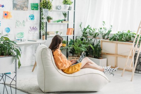 Photo for Young woman using laptop while sitting on soft chaise lounge in light spacious room - Royalty Free Image