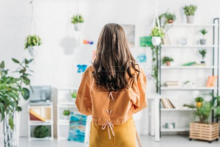 Photo pour Vue arrière de jeune femme restant dans la pièce spacieuse à la maison - image libre de droit