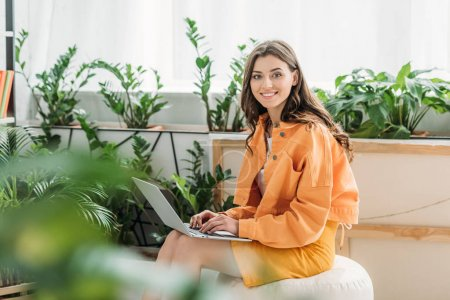 selective focus of cheerful woman surrounded by green plants smiling while using laptop at home