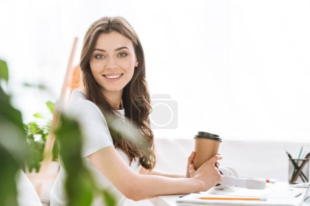 Photo for Selective focus of attractive young woman holding disposable cup, smiling and looking at camera - Royalty Free Image