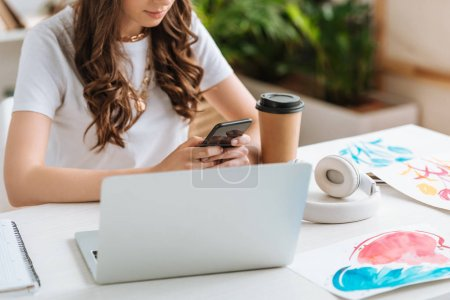 Photo for Cropped shot of young woman using smartphone while sitting near laptop and disposable cup - Royalty Free Image