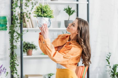 Photo for Pretty young woman touching flowerpot while standing near rack in spacious room - Royalty Free Image