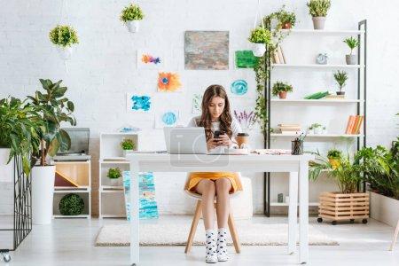 Photo pour Jolie jeune femme utilisant le smartphone tout en s'asseyant dans la salle spacieuse avec les usines vertes et les peintures sur le mur - image libre de droit