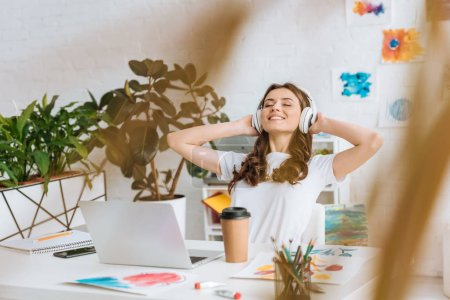 Photo for Selective focus of happy girl in headphones stretching while sitting at desk near laptop, disposable cup and paintings - Royalty Free Image