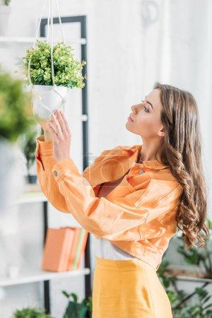 Foto de Enfoque selectivo de la mujer hermosa pensativa en la ropa naranja tocando maceta - Imagen libre de derechos