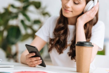 Photo for Selective focus of young woman in headphones using smartphone while sitting near disposable cup - Royalty Free Image