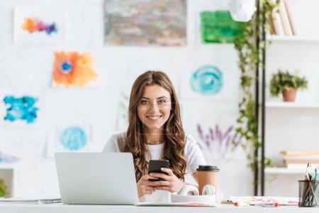 Photo for Cheerful woman looking at camera while sitting at desk near laptop and using smartphone - Royalty Free Image