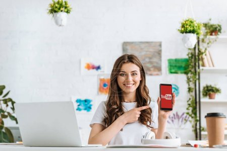 Photo pour KYIV, UKRAINE - APRIL 17, 2019: Cheerful young woman looking at camera and pointing with finger at smartphone with Skype app on screen. - image libre de droit