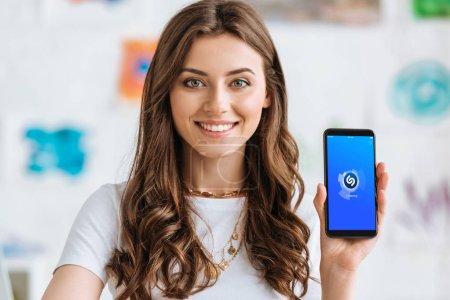 Photo pour KYIV, UKRAINE - 17 AVRIL 2019 : Belle fille regardant la caméra et montrant smartphone avec l'application Shazam à l'écran . - image libre de droit