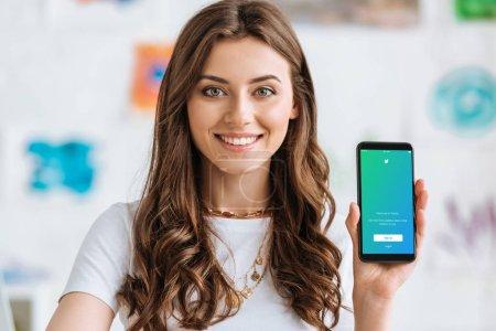 KYIV, UKRAINE - 17 AVRIL 2019 : Joyeux jeune femme regardant la caméra et montrant smartphone avec application Twitter à l'écran .