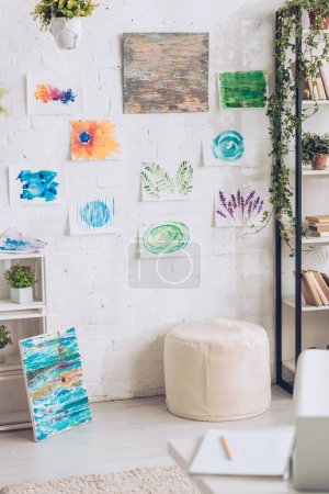 Foto de Light room with green potted plants and colorful painting on white wall - Imagen libre de derechos