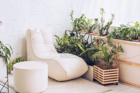 Photo for White soft chaise lounge and pouf in room with lush green plants - Royalty Free Image