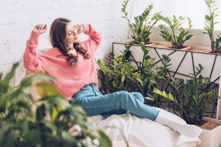 Foto de Enfoque selectivo de la mujer joven bonita que se extiende mientras se sienta en la habitación cerca de exuberantes plantas verdes - Imagen libre de derechos