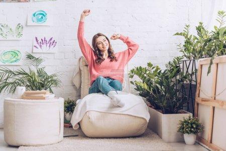 Foto de Chica sonriente estirando mientras se sienta en un suave chaise lounge cerca de puf y exuberantes plantas verdes - Imagen libre de derechos