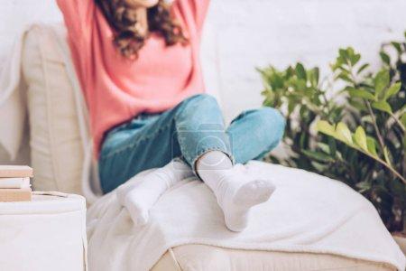 Foto de Vista recortada de la joven sentada en suave chaise lounge blanco - Imagen libre de derechos